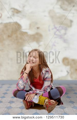 a young teenager sitting cross-legged on the floor