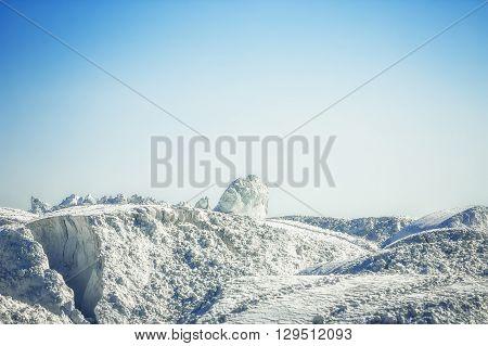 White mountain of gypsum on development under the blue sky.