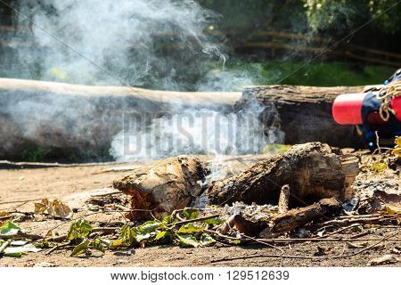 Outdoor leisure camping survival concept. Fireplace in forest clearing. Smoking wood.