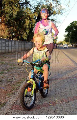 Rustenburg Marathon Club Rainbow Run - NOVEMBER 25: Mom and son on bicycle covered with powder paint at colour run on November 25 2015 Rustenburg South Africa.