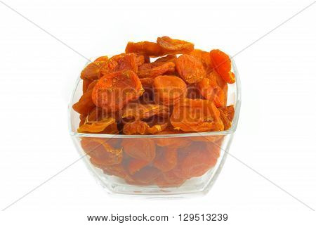 Dried apricots in a glass dish on a white background