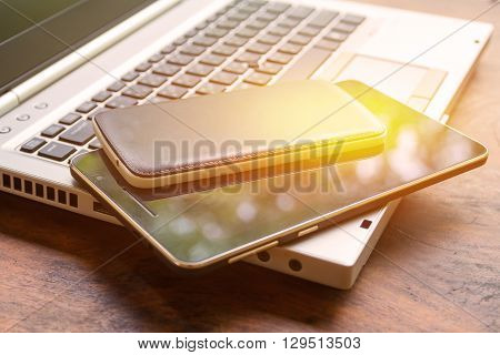 laptop with tablet and smart phone on wood table.