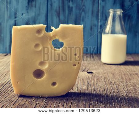 closeup of a piece of Swiss cheese and a glass bottle with milk on a rustic wooden table, against a blue rustic wooden background