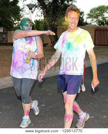 Rustenburg Marathon Club Rainbow Run - NOVEMBER 25: Woman throwing husband with yellow powder paint at colour run on November 25 2015 Rustenburg South Africa.