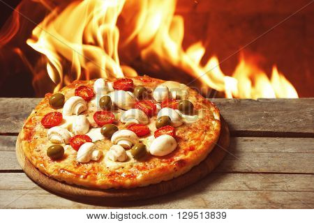 Tasty hot pizza with mushrooms and tomatoes on wooden table against fire flame background