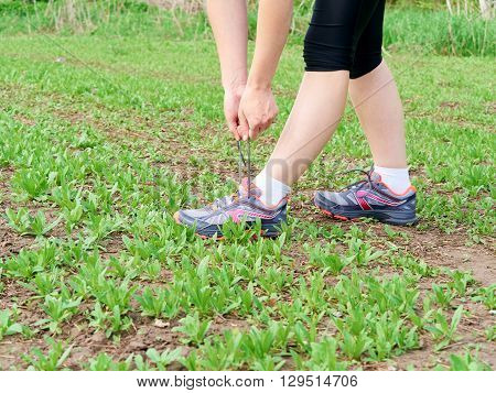 Woman Athlete Tying Running Shoes.
