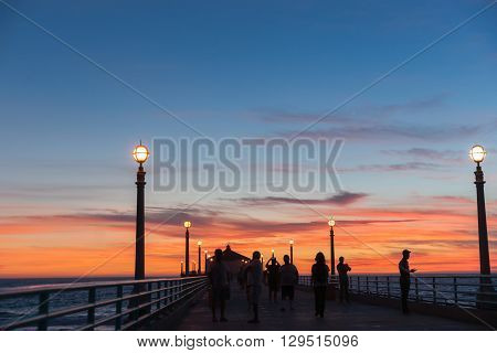 People unrecognizable in silhouette on Manhattan Beach Pier Californian nights at the pier at sunset as sun goes down and lights come on