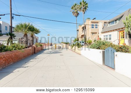 Residential lane lined by fences homes and gates in seaside town Hermosa Beach California USA