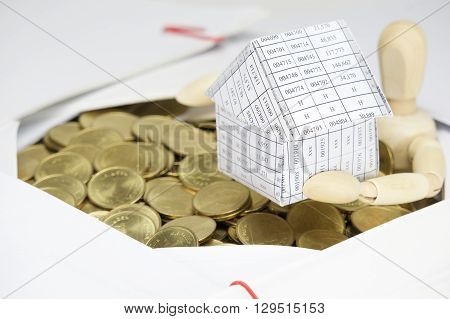 Close Up Wooden Dummy Holding House Surrounded By Gold Coins