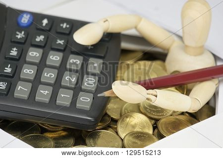Wooden Dummy Holding Pencil With Calculator Have Surrounded By Coins