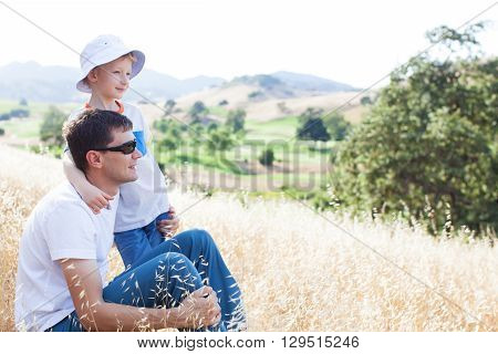 family of two enjoying rest after hiking together in beautiful california hills father and son day activity together