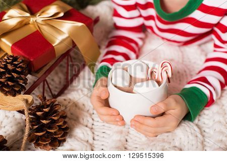 close-up of delicious hot chocolate with marshmallows and candy canes at home with christmas decorations
