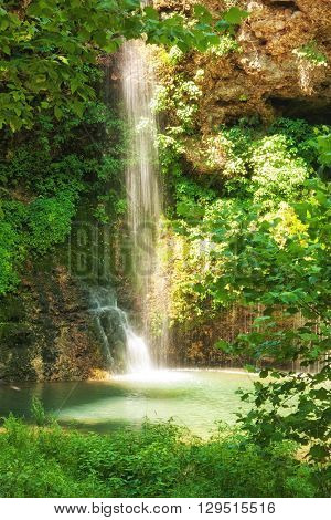 Natural, romantic, partially shaded waterfall running into a small pool, surrounded by trees
