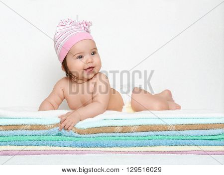 baby portrait in diaper on towel at studio, white background