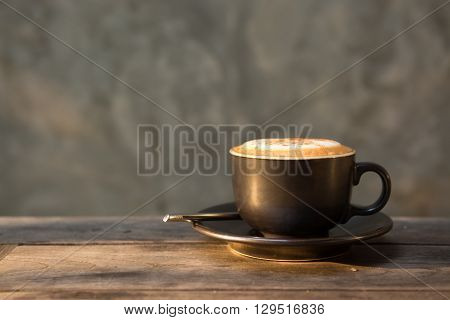 Hot cappuccino coffee cup on wooden table in thea sunlight in morning time