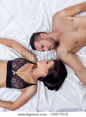 Love and sex. Top view of beautiful loving couple lying in bed