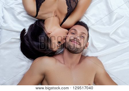 Top view of man pretty smiling while sexy woman kissed him