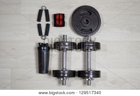 Dumbbells with expander and shaker on the on a wooden floor