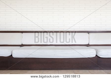 White Sofa With Cushions And White Brick Wall