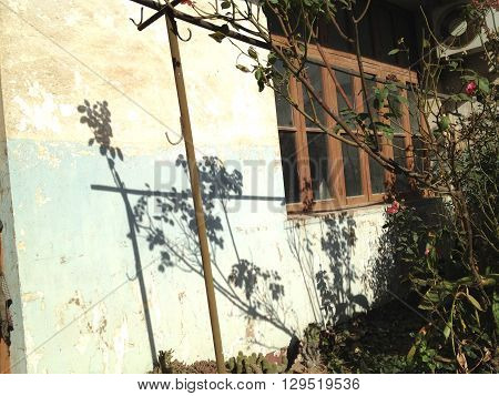 A partial view of outside of a deserted old house in the countryside.