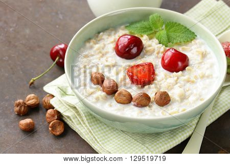 oatmeal porridge with milk and  berries- healthy, funny breakfast