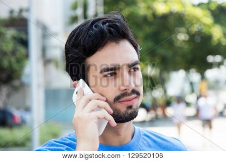 Thinking hispanic guy listening at phone outdoor in the city with buildings in the background