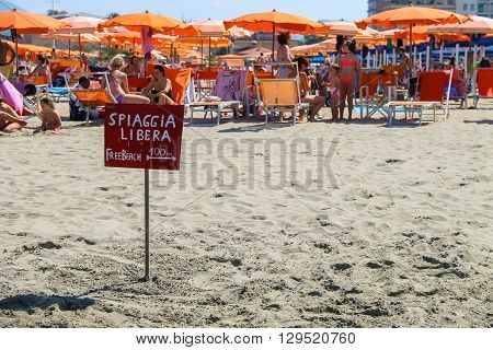 Viareggio Italy - June 28 2015: A pointer to the free beach near resting people. Viareggio is the famous resort on the coast of the Ligurian Sea