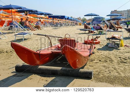 Viareggio Italy - June 28 2015: Catamaran on the beach near the resting people. Viareggio is the famous resort on the coast of the Ligurian Sea