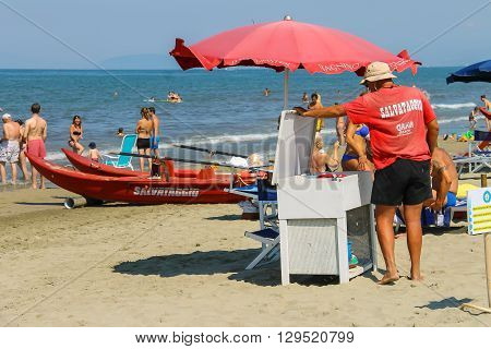Viareggio Italy - June 28 2015: Beach lifeguard surrounded by resting people. Viareggio is the famous resort on the coast of the Ligurian Sea