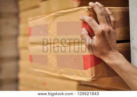 Delivery man resting his hand on the goods. Hand of a delivery man is in sharp focus and the packing boxes are ready to deliver, no human face is visible in the frame.