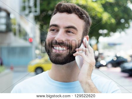Laughing caucasian man with beard at phone outdoor in city