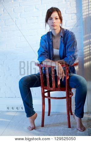 Casual young woman sitting on chair backwards, thinking.