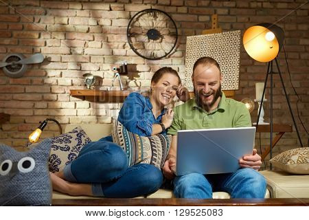 Happy couple using laptop computer at home, sitting on sofa, laughing.