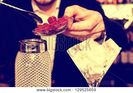 Bartender is putting fresh raspberries to a silver shaker, toned image