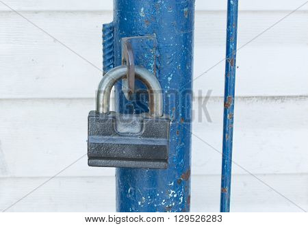 Gray padlock in the closed state on the blue fence. Close-up.
