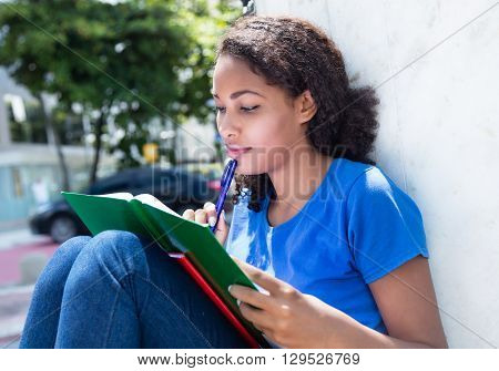 Learning latin female student with curly hair outdoor in the city