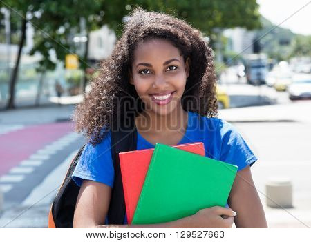 Laughing latin female student with curly hair outdoor in the city