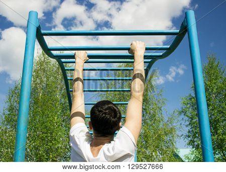 young man doing pull-ups on horizontal bar