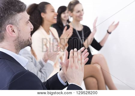 Shot of a team of businesspeople clapping hands while having a meeting