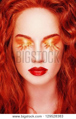 Portrait of young beautiful redhead woman with fancy feather false eyelashes and red lipstick