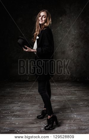 Joyful pretty girl wearing black classic hat smiling at camera. Hipster style.