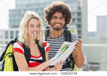 Portrait of young couple holding map on terrace