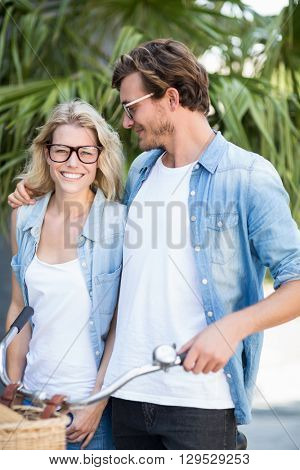 Happy young couple in spectacles standing with bicycle