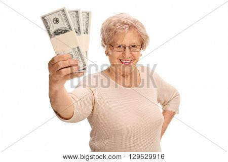 Joyful mature lady holding a few stacks of money and looking at the camera isolated on white background