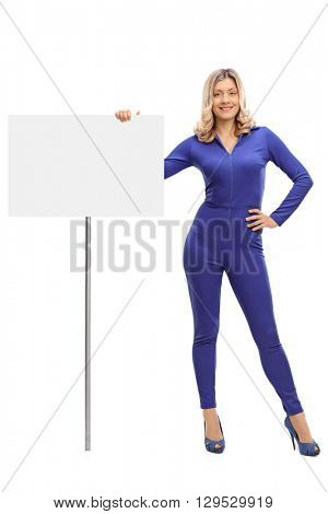 Full length portrait of an attractive young woman standing next to a blank signboard isolated on white background