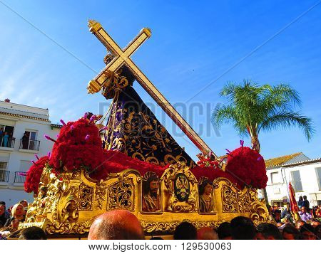 Alora Spain 25 March 2016: Jesus with large cross carried through village in Easter procession. Alora Spain 25 March 2016