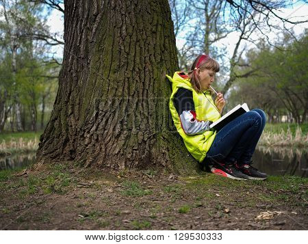 Teen girl in the park with a book. Concept - exam preparation, difficulty learning, school. The girl has her hair dyed red. Bright jacket. Park, spring or autumnTeen girl in the park with a book. Concept - exam preparation, difficulty learning, school. Th