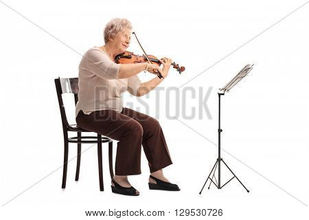 Mature female violinist playing a violin seated on a wooden chair isolated on white background