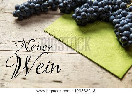 Blue grapes on wooden table german text Neuer wein which means federweisser or young wine