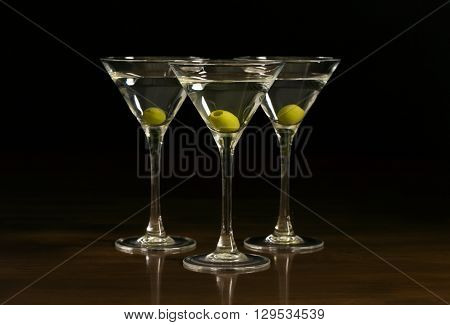 Three glasses with a martini cocktail on a black background